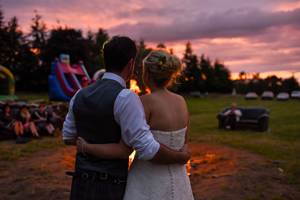 couple watching bonfire on their wedding day