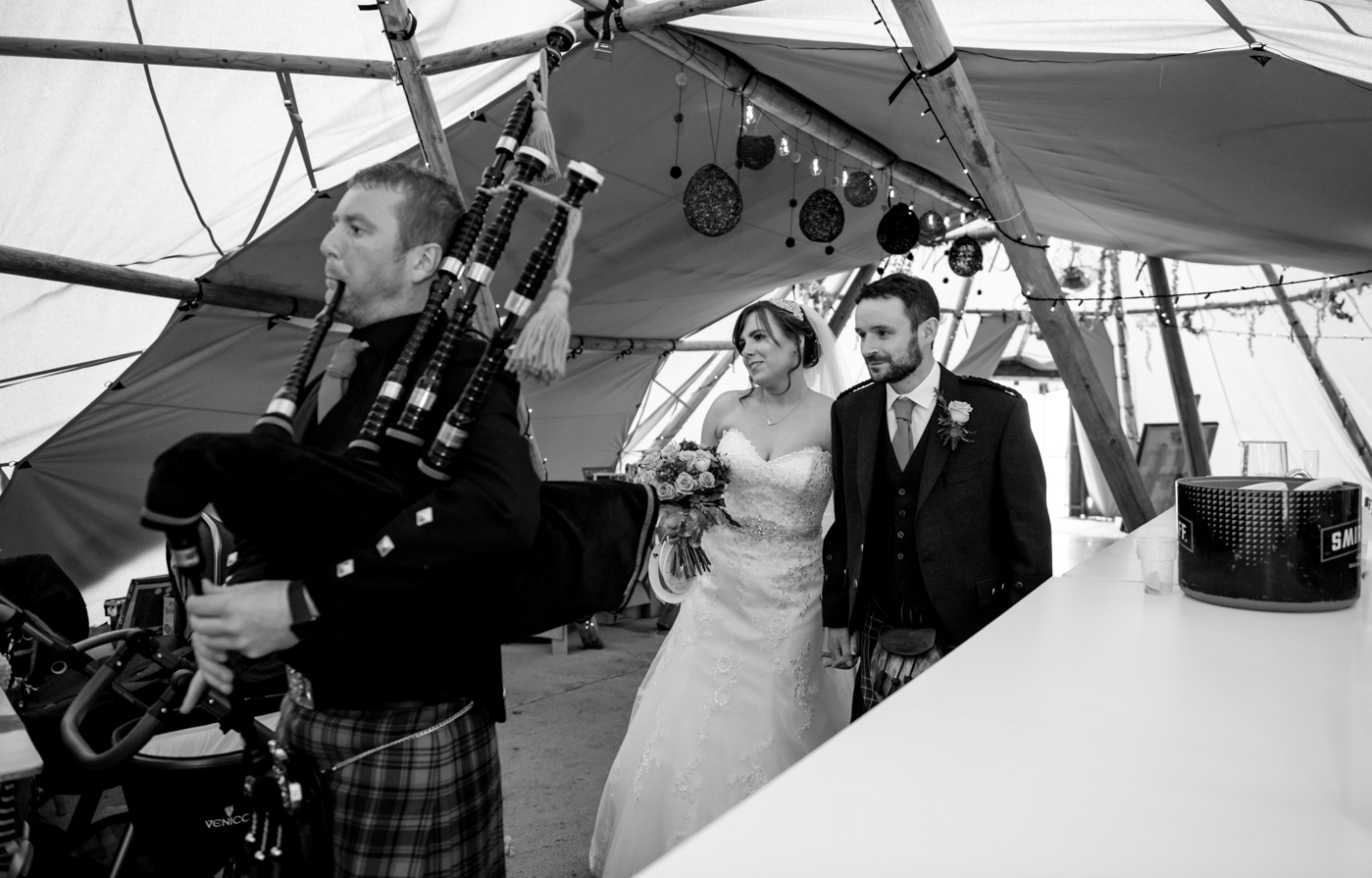 bride and groom getting piped into tipi